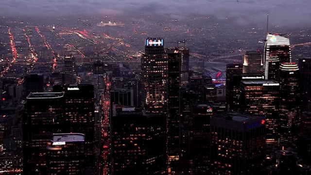 los angeles skyline lights up at night with fog over the skyscrapers in celebration of the rams playoffs in january, 2018. - playoffs stock videos & royalty-free footage