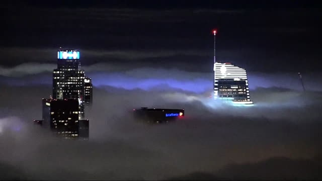 los angeles skyline lights up at night with heavy fog over the skyscrapers in celebration of the rams playoffs in january, 2018. - produced segment stock videos & royalty-free footage