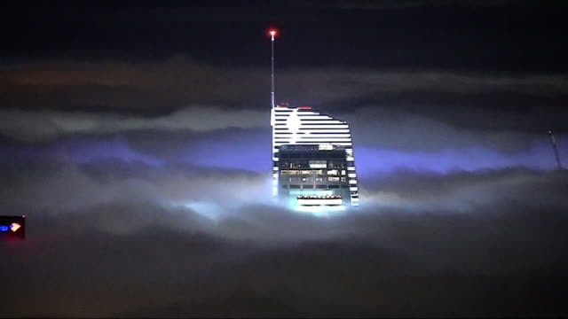 los angeles skyline lights up at night with heavy fog over the skyscrapers in celebration of the rams playoffs in january, 2018. - playoffs stock videos & royalty-free footage