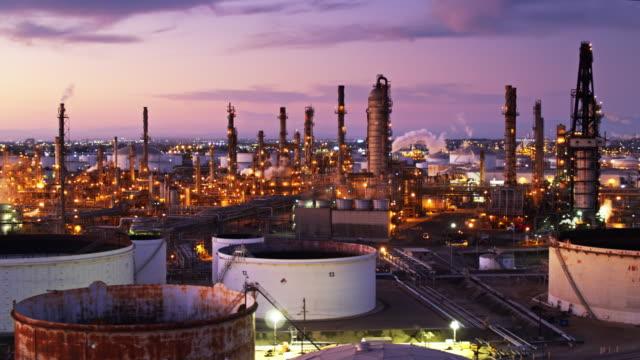 vídeos de stock e filmes b-roll de los angeles sprawl glowing behind oil refinery at sunset - drone shot - wilmington cidade de los angeles