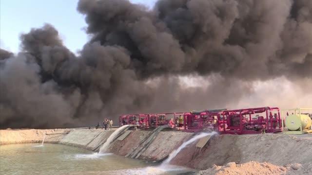 vídeos de stock, filmes e b-roll de los bomberos aparecen agotados en medio de una espesa columna de humo negro que emana de un pozo petrolero incendiado por el grupo yihadista estado... - irak
