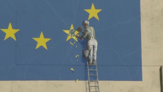 los camiones pasan junto a un mural que representa a un hombre cortando una bandera de la union europea en la ciudad portuaria de dover donde la... - entrada stock videos and b-roll footage