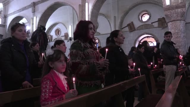 vídeos de stock, filmes e b-roll de los crisitianos iraquies celebraron una agridulce navidad en quarash un destruido pueblo cercano a mosul del cual huyeron los ultimos dos anos por la... - irak