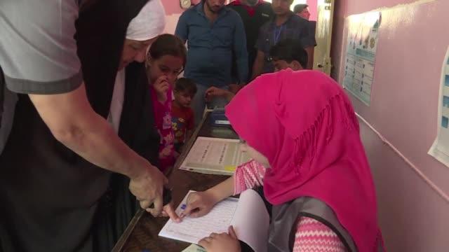 vídeos de stock, filmes e b-roll de los iraquies votaron el sabado para elegir un nuevo parlamento que tendra que supervisar la reconstruccion de un pais devastado despues de tres anos... - irak
