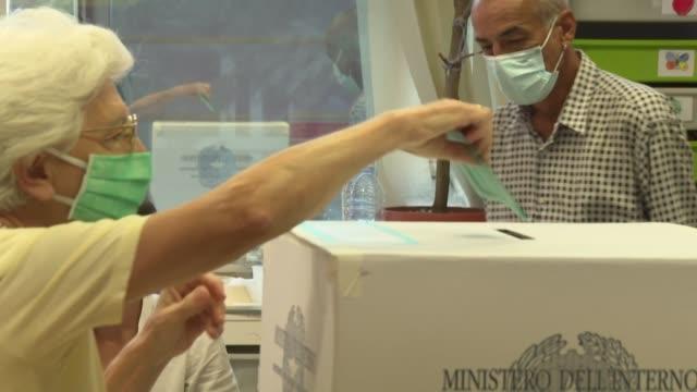 vídeos y material grabado en eventos de stock de los italianos desafiaron tímidamente el domingo el avance del coronavirus para votar en referéndum y elecciones regionales, particularmente... - a la izquierda de