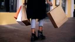 lose up of woman legs wearing stylish black coat and jeans at day time hold colored shopping bags after big shopping day. Fashion shopper shopaholic in slow motion. Rare view
