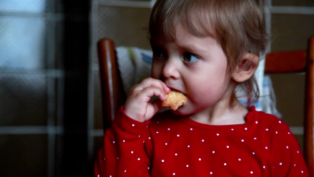 Сlose-up van een baby eten cookie en wordt gewezen op de linkerzijde