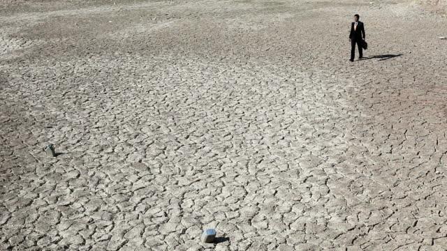 vidéos et rushes de lost homme d'affaires dans le désert pour vous aider à - sec