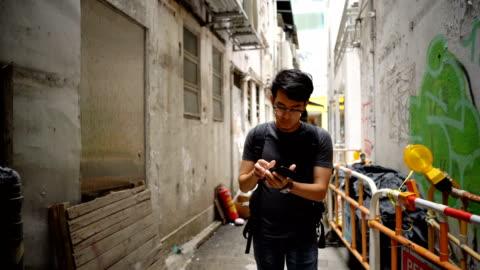 vidéos et rushes de marche d'homme perdu quelque part dans la ville - montrer la voie