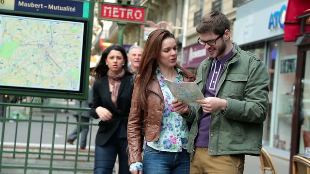 Lost tourist couple look at map of Paris and argue about which direction to go.
