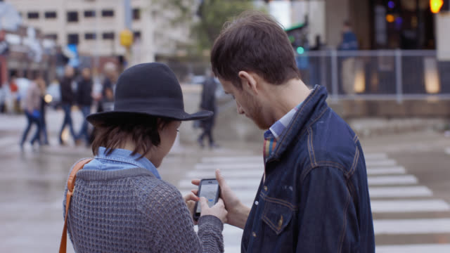 Lost young couple wander through downtown Austin and stop at crosswalk to look at directions on smartphone
