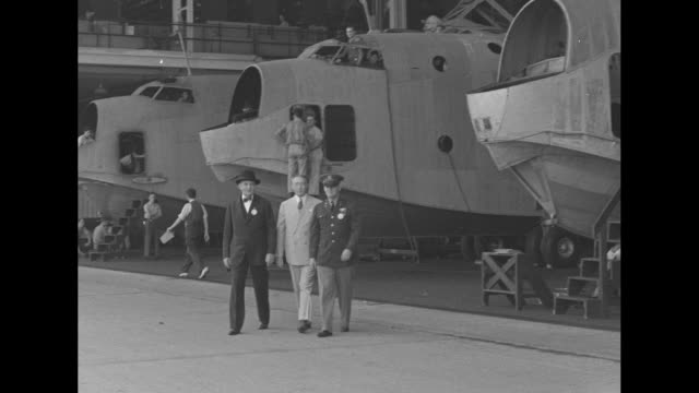 Lot full of parked cars in front of plane factory / automotive industry executive William Knudsen with General Henry Arnold walking inside plant...