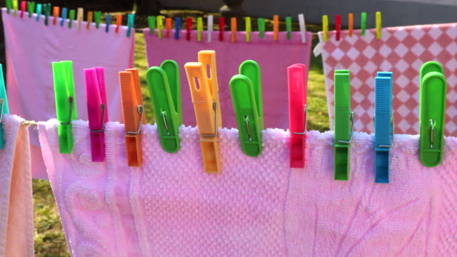 a lot of colorful laundry tweezers in the clothesline on the sun in a creative composition. - clothes peg stock videos & royalty-free footage