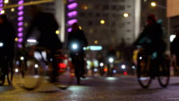 Lot of cyclists ride during night cycling bike, bicycle parade in blur by illuminated night city street timelapse. Crowd of people on bike. Bike traffic. Concept sport healthy lifestyle. Bright shining lights. Low angle view