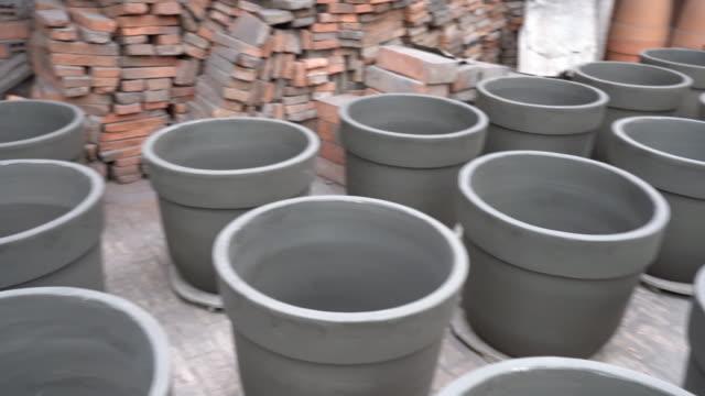 eine menge von blumentopf keramik vor brennenden in fabrik - stahlfass stock-videos und b-roll-filmmaterial