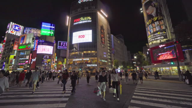 vidéos et rushes de beaucoup de gens à l'intersection de quartier de shibuya à tokyo au japon - billboard