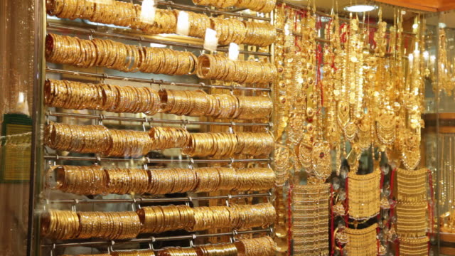 ms lots of gold bangles and jewelry hanging in jewellry shop / dubai,  united arab emirates - gold coloured stock videos & royalty-free footage