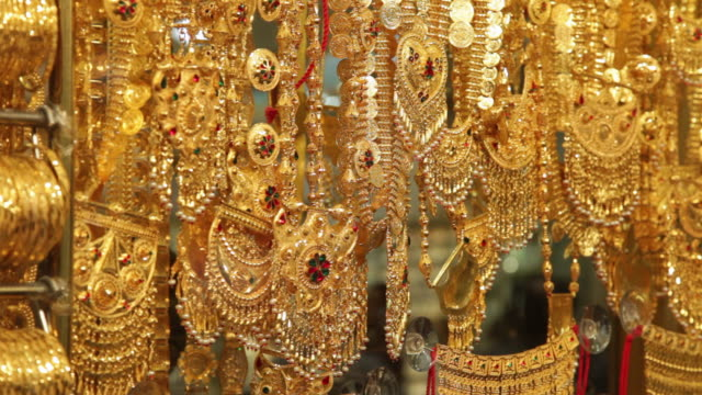 cu tu lots of gold bangles and jewelry hanging in jewellry shop / dubai,  united arab emirates - necklace stock videos & royalty-free footage
