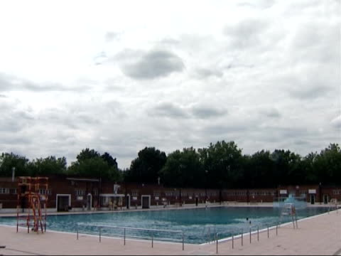 lottery funds secure the restoration of two lidos; woman sunbathing next to pool cloudy sky tilt down to general view of recently restored parliament... - parliament hill stock videos & royalty-free footage