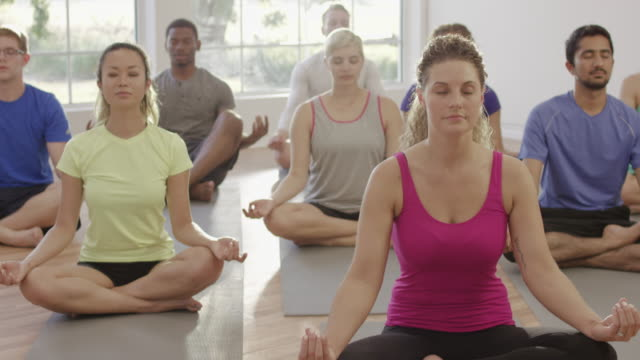 lotus position in yoga class - lotus position stock videos & royalty-free footage