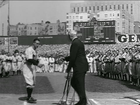 Lou Gehrig shaking hands with man in suit in crowded stadium / farewell