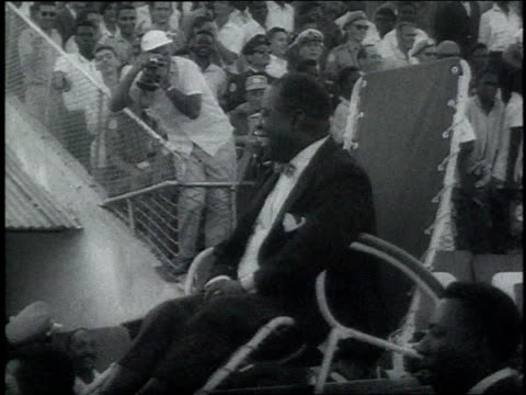 louis armstrong being carried on a chair during a parade in his honor in africa / crowds gathering to hear louis armstrong perform / policemen... - 1960 stock videos & royalty-free footage