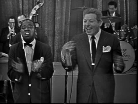 vídeos y material grabado en eventos de stock de louis armstrong danny kaye singing together on stage in front of band / television show - instrumento de cuerdas