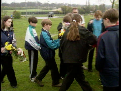 Louise Allen Killiing ENGLAND Northants Corby MS Schoolchildren towards across grass carrying flowers PULL OUT and PAN LR as lay them at spot where...