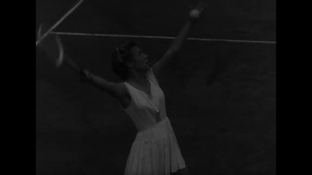 VS Louise Brough and Doris Hart play tennis / spectators / winning point by Brough they shake hands over net / Brough with flowers