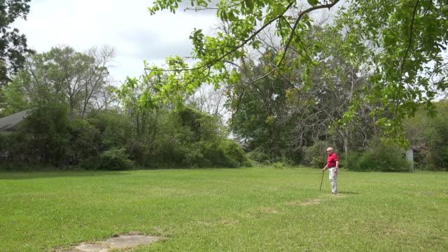 Louisiana man walks on lawn with a cane