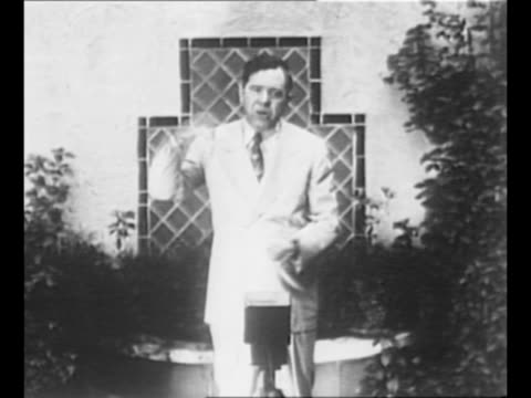 louisiana politician huey long approaches camera in shady area on grounds of house stops / long speaks gesturing flamboyantly / long standing holds... - kapitol von louisiana stock-videos und b-roll-filmmaterial