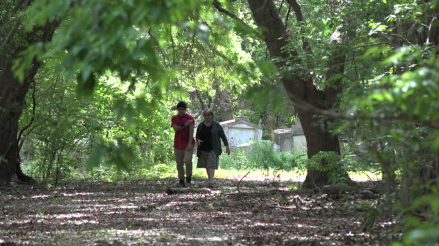 louisiana woman and boy walking from tombs in woods - one teenage boy only stock videos & royalty-free footage