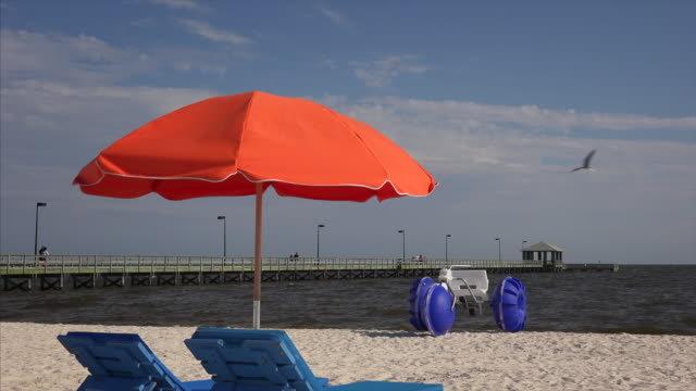 lounge chairs and beach umbrella along mississippi gulf coast in biloxi - beach umbrella stock videos and b-roll footage