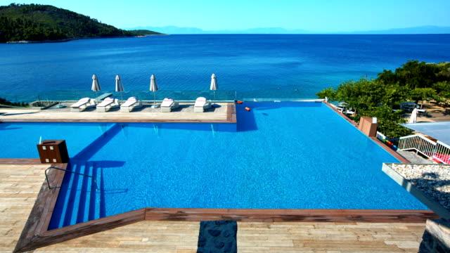 ラウンジチェアとパラソルを スコペロス島 島のプール - 高級ホテル点の映像素材/bロール