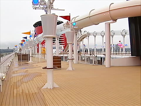 ms of lounge chairs on deck and cut to cu shot of the mickey mouse shape logo on the side of the ship the camera pans left to the top of the deck... - water slide stock videos & royalty-free footage