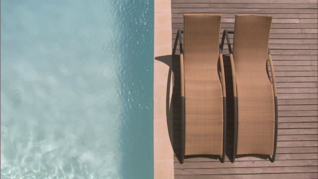 oh ms lounge chairs on edge of wooden deck by swimming pool/ cape town, south africa - chair stock videos & royalty-free footage