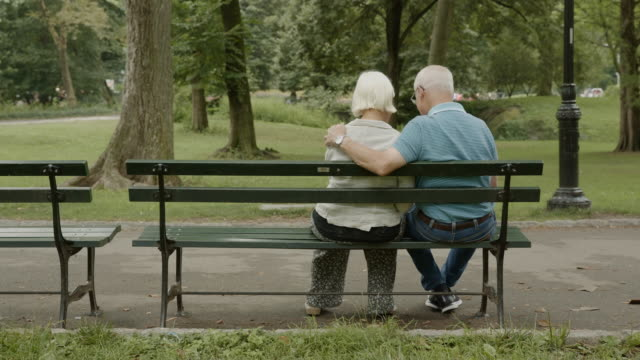 Love bench smartphone social media New York surfing net senior couple
