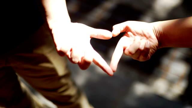 liebespaar herz form durch die hände auf der straße. - hoffnung stock-videos und b-roll-filmmaterial