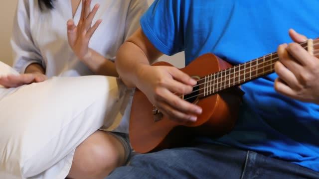 vídeos de stock, filmes e b-roll de casal de amor tocando cavaquinho e guitarra na cama - ukulele