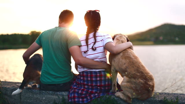 Love couple with their dogs on the lake