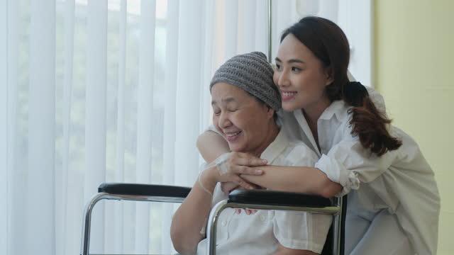 vídeos de stock, filmes e b-roll de emoção amorosa, uma velha que sofre de câncer usando um lenço sentado em uma cadeira de rodas, sua filha abraçada com amor. - clínica médica