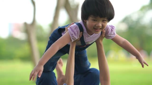 stockvideo's en b-roll-footage met love eternity concept, moeder en dochter spelen vliegend vliegtuig samen in de tuin - peuterschool gebouw