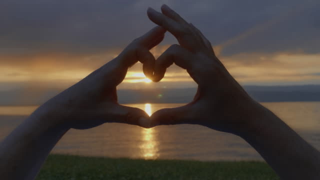 Love heart hands. Sunset over water.