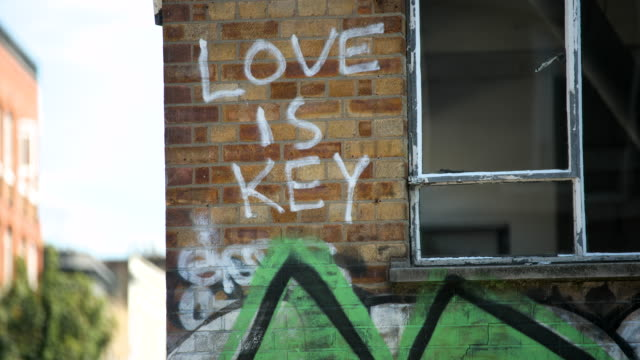 'love is key' graffiti on brick wall - western script stock videos & royalty-free footage