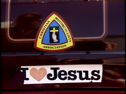 'i love jesus' and 'christian motocyclists association' bumper sticker on the back of a motorcycle - sticker stock videos and b-roll footage