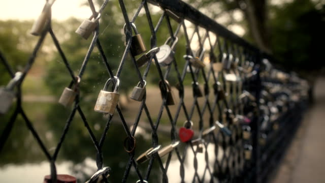 love locks on bridge at sunset - fence stock videos & royalty-free footage