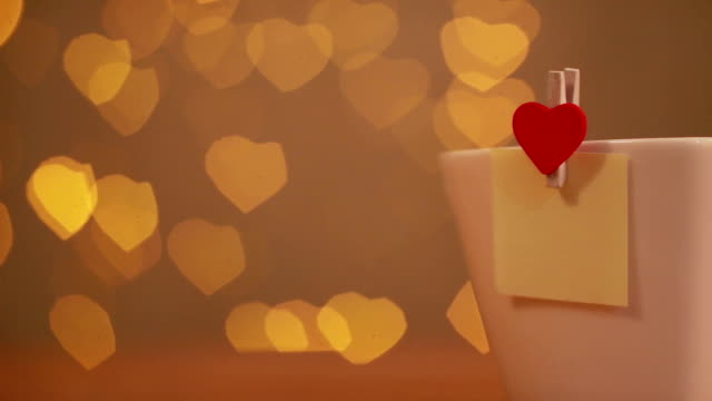 love note on cup with heart flare background