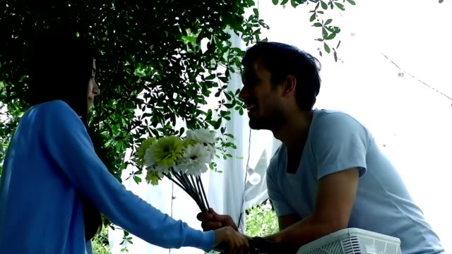 Love, romance and flowers.Man making proposal to woman with flower for wedding.HD format.