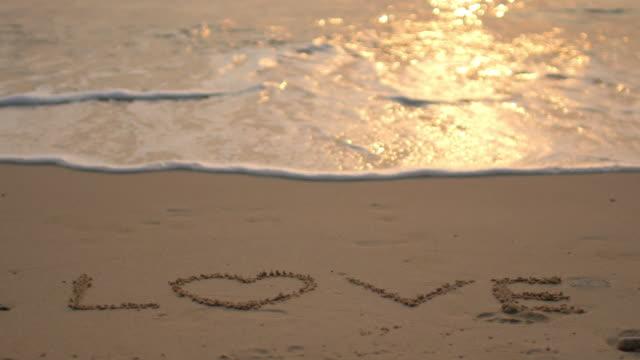 Liebe Wort Schreiben am Strand mit Welle des Meeres