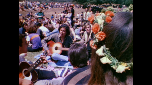 / lovein at tapia park / man and women in front of microphones / men sitting on floor playing guitar / flower children listen to musicians / people... - 1968年点の映像素材/bロール
